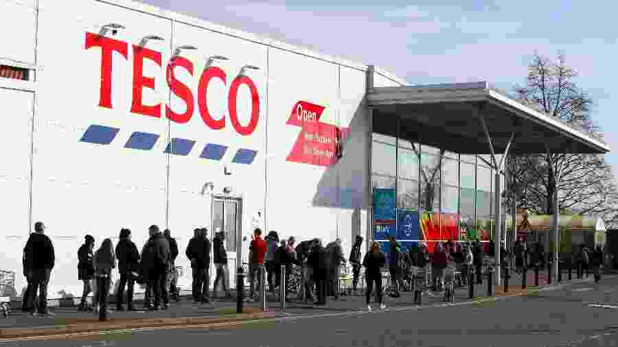 22.mar.2020 - Pessoas na fila do supermercado Tesco, na Inglaterra - Nick Potts / PA Images via Getty Images
