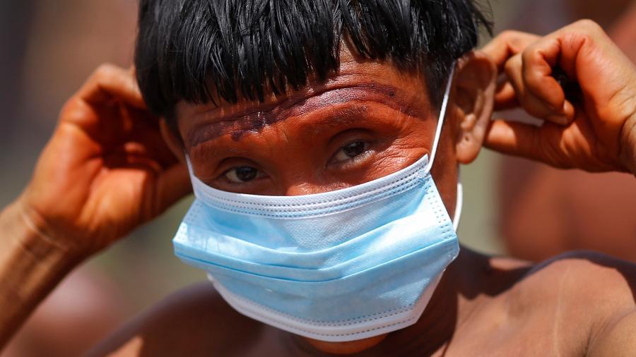 Indígena do povo ianomâmi segura máscara de proteção em Alto Alegre, Roraima -