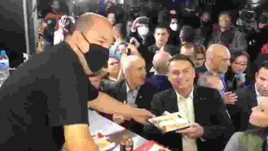 O presidente Jair Bolsonaro (sem partido) posa sem máscara em meio a aglomeração - Reprodução
