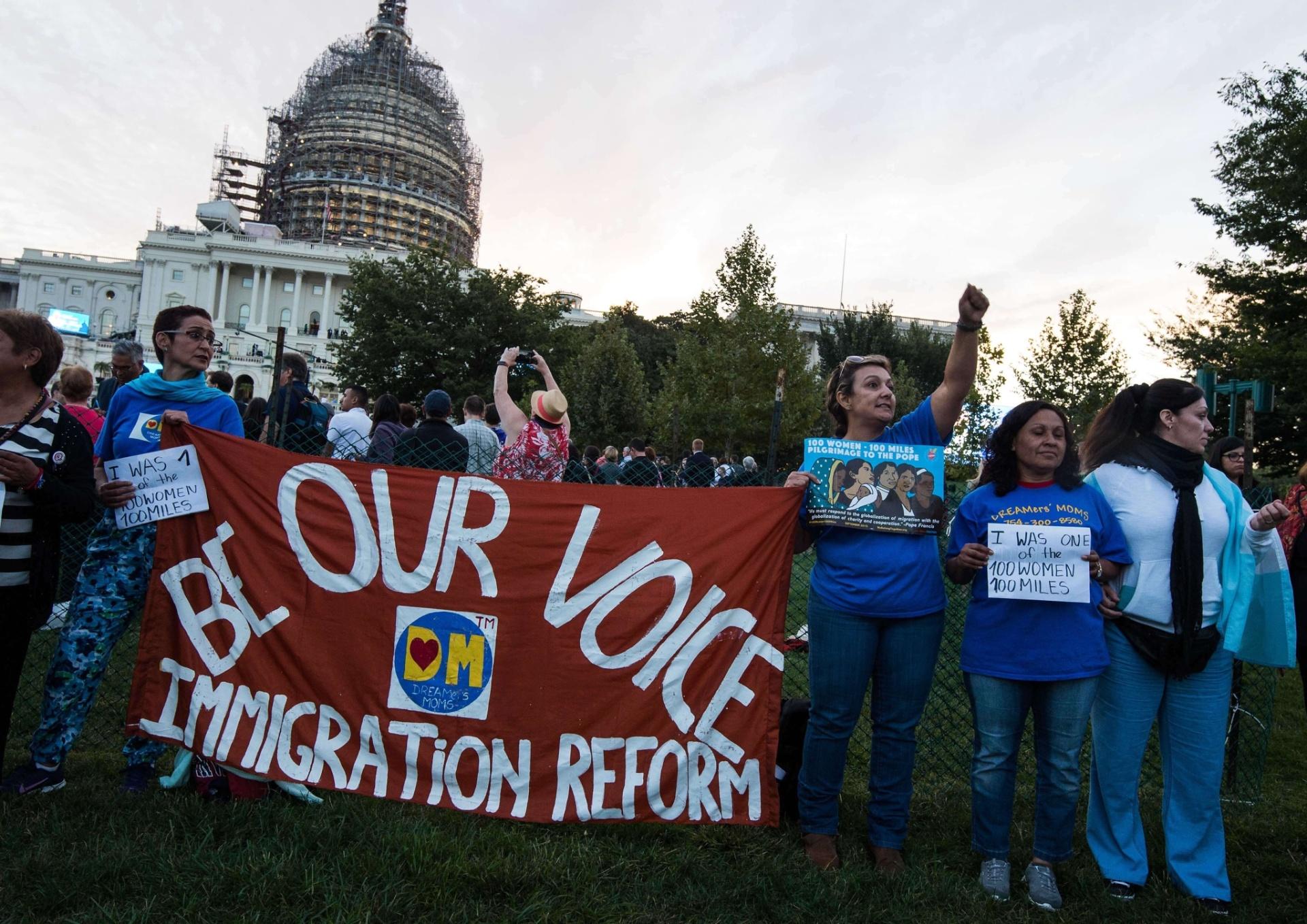 24.set.2015 - Ativistas favoráveis à reforma de imigração norte-americana seguram faixa na frente do Capitólio, em Washington, antes de reunião do papa Francisco no Congresso dos EUA. Na faixa vermelha lê-se