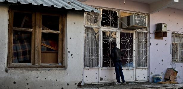 Garoto curdo olha para dentro de sua casa cheia de buracos de bala depois de conflitos armados entre membros do PKK e Forças Armadas turcas