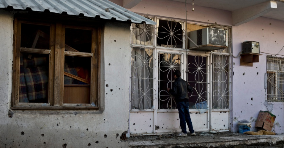 10.jan.2016 - Garoto curdo olha para dentro de sua casa cheia de buracos de bala depois de conflitos armados entre membros do PKK (Partido Trabalhista do Curdistão) e Forças Armadas turcas