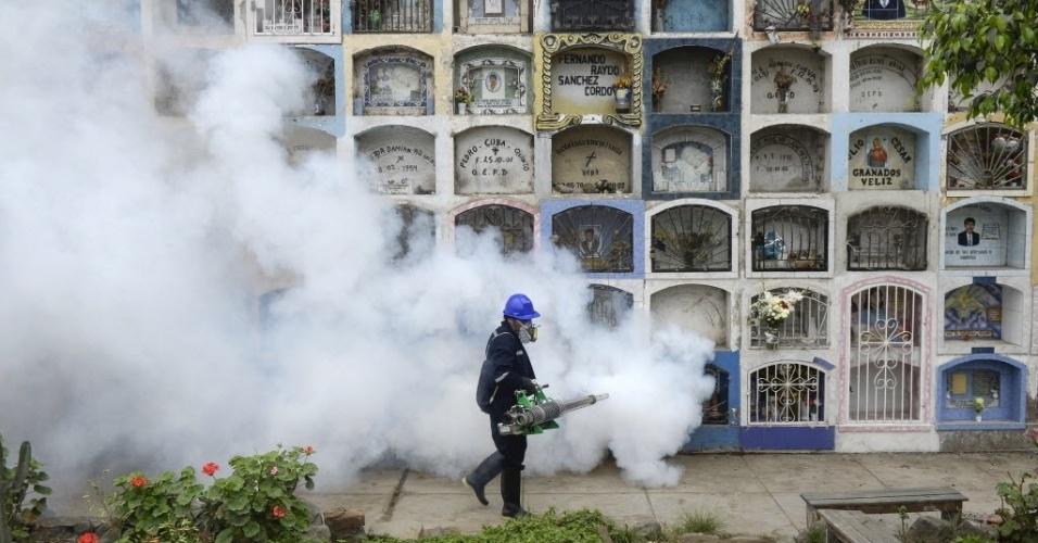 """15.jan.2016 - Um homem caminha pelo cemitério Nueva Esperanza, na periferia de Lima, Peru, enquanto encobre o local de fumaça em um procedimento de dedetização da área. As autoridades de saúde determinaram o uso de inseticidas para evitar o aumento das doenças chikungunya e zika vírus, transmitidas pelo mosquito """"Aedes aegypti"""""""