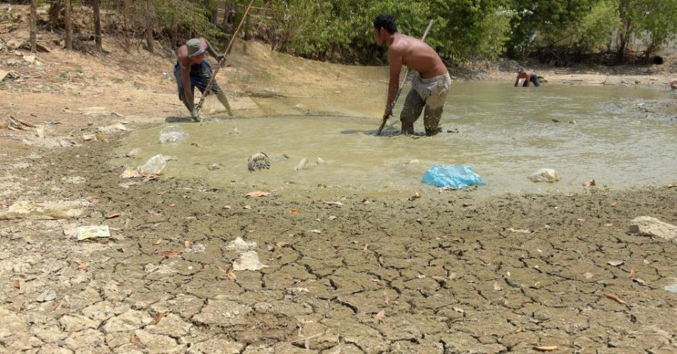 27.abr.2016 - Homens pescam com rede em lago quase seco na província de Kandal, no Camboja. O primeiro-ministro do país emitiu um apelo a outras autoridades para mobilizar a população a racionar água para enfrentar a pior seca dos últimos quarenta anos