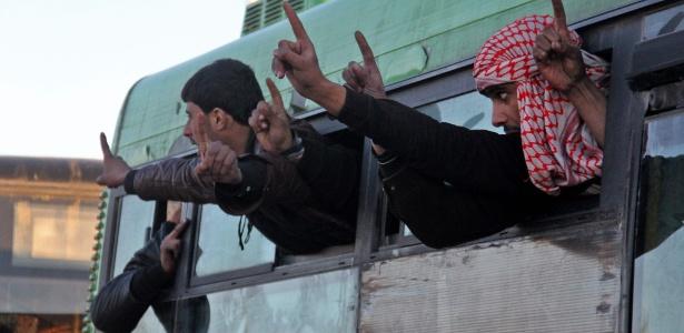 Sírios que foram evacuados acenam ao chegar em posto de controle na região oeste de Aleppo - Omar haj kadour/ AFP