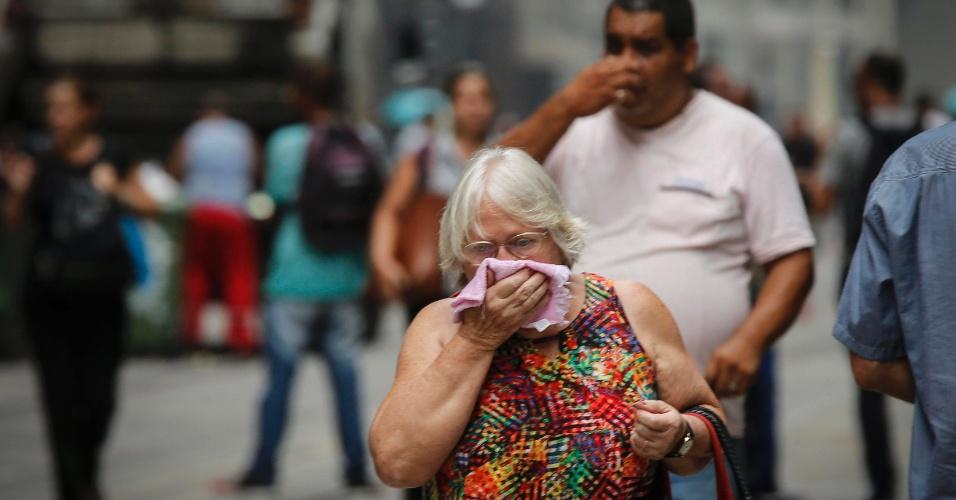 9.fev.2017 - Pedestres se protegem contra o efeito do gás lacrimogênio lançado por policiais militares durante confronto com manifestantes nas imediações da Alerj, no Centro do Rio