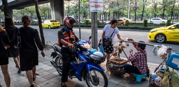 Um mototaxista aguarda passageira comprar comida de um vendedor de rua em Bangcoc