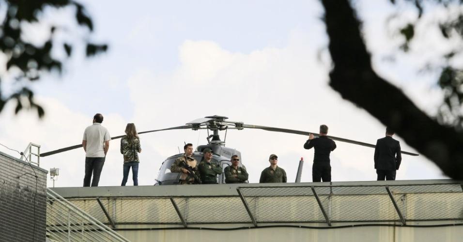 Policiais posam para foto em frente helicóptero no telhado da Polícia Federal em Curitiba