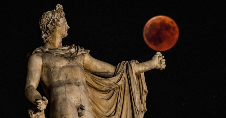 27.jul.18 - A lua de sangue ao lado da estátua de Apollo, em Atenas, na Grécia