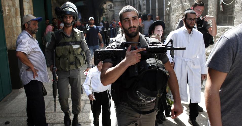 15.set.2015 - Forças de segurança israelenses escoltam judeus vindos do Muro das Lamentações, local considerado sagrado pelo judaísmo, enquanto eles cruzam o bairro muçulmano na Cidade Velha de Jerusalém. Muçulmanos e a polícia israelense entraram em confronto na região da mesquita de Al-Aqsa, em Jerusalém, no terceiro dia da celebração do ano novo judaico