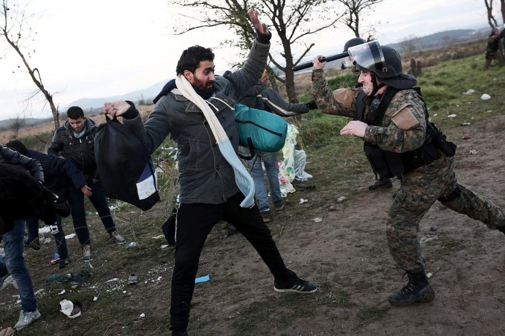 26.nov.2015 - Policial macedônio agride refugiado. Mais de 200 pessoas tentaram abrir uma brecha na cerca de arame farpado na fronteira entre a Grécia e a Macedónia e atiraram pedras contra os policiais