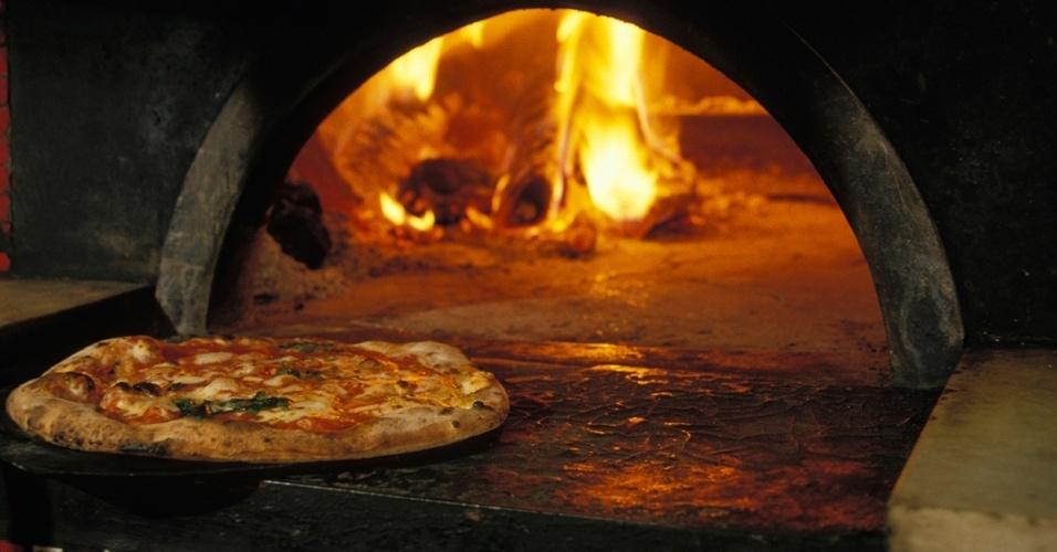 24.fev.2016 - Uma pizza sai do forno de pedra num restaurante em Roma, na Itália. Apesar de Nápoles ser a origem da pizza moderna, ela é popular em todo o país