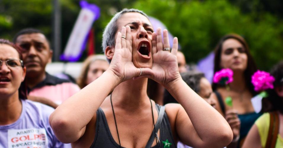 8.mar.2016 - Com broches do PT e adesivos pelos direitos feministas, mulher grita durante protesto na avenida Paulista, em São Paulo, organizado por movimentos feministas e sindicalistas. Ação ocorre no Dia Internacional da Mulher