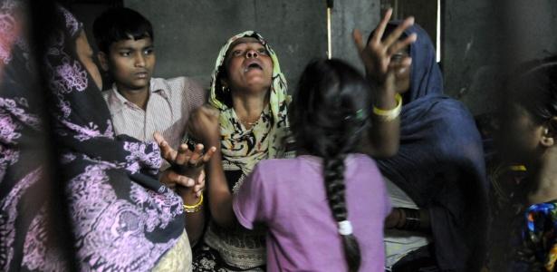 Mãe (centro) de adolescente morta após ser estuprada e incendiada chora durante seu funeral em Greater Noida, próximo a Nova Déli (Índia)