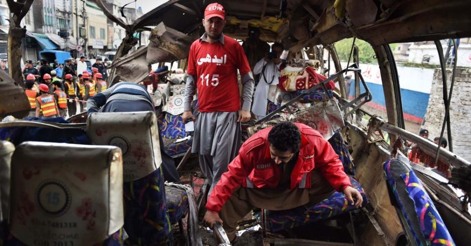 16.mar.2016 - Voluntários vasculham os destroços de um ônibus destruído por explosão na cidade de Peshawar, no Paquistão. Pelo menos 16 pessoas morreram e dezenas de outras ficaram feridas no atentado, atribuído a insurgentes contrários ao governo central do país