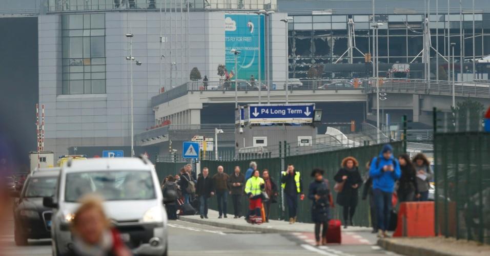 22.mar.2016 - Pessoas correm após forte explosão no aeroporto internacional de Bruxelas. Ao fundo, é possível observar janelas danificadas na área de embaque