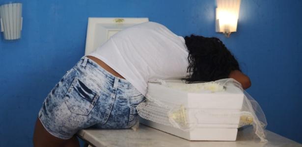 Tayane Pereira da Silva, 20, abraça caixão com o corpo do filho Ryan Gabriel -  Fabiano Rocha / Extra / Ag. O Globo