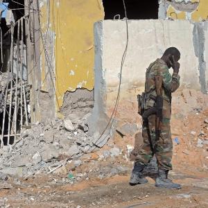Soldado fala ao telefone perto de destroços do ataque terrorista no sábado em um hotel de Mogadício, capital da Somália
