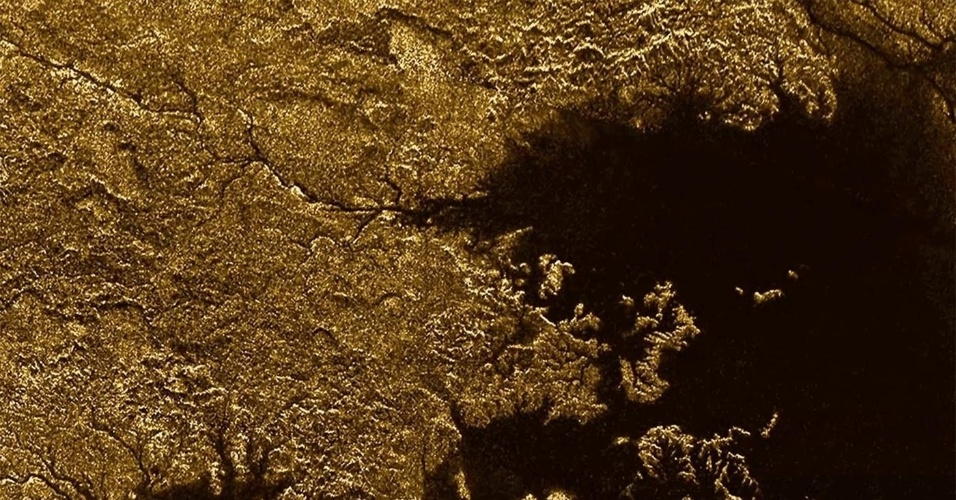 CÂNIONS DE TITÃ - Terreno recortado pela ação de mares e rios passando entre desfiladeiros. A imagem poderia ser de alguma região da Terra, mas é de Titã, a maior lua de Saturno. Os mares, rios e lagos de metano do satélite natural provocam a erosão da superfície. No quadrante superior esquerdo da imagem, feita pela sonda Cassini, é possível ver o rio Vid Flumina, que flui para o mar Ligeia (mancha escura na direita). Pesquisadores revelaram que os canais do Vid Flumina possuem pouco menos de um quilômetro de largura, até 570 metros de profundidade e declives superiores a 40°. Descobrir como eles se formaram pode ajudar a entender processos geológicos semelhantes na Terra