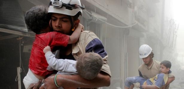 Membros da Defesa Civil socorrem crianças após ataque em Aleppo