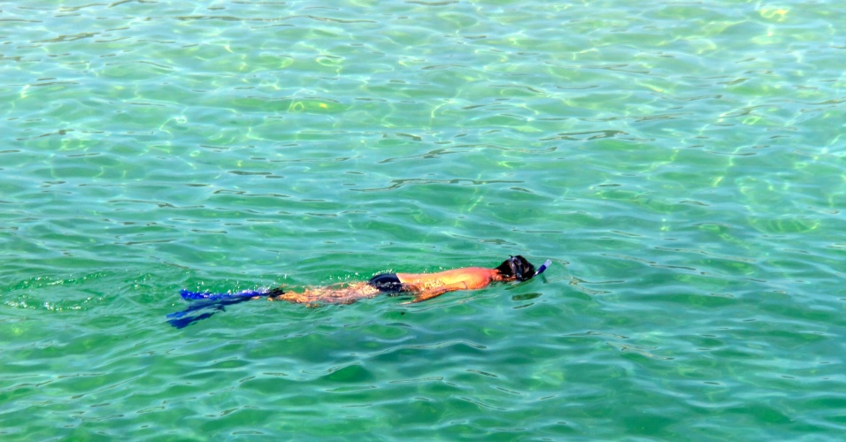 27.dez.2016 - O banhista se desliga da areia da praia do Arpoador, na zona sul do Rio de Janeiro, e se concentra no mar para evitar o calor. A capital registrou hoje sua maior temperatura em 2016: 42°C
