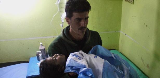4.abr.2017 - Criança inconsciente é carregada até hospital em Khan Sheikhun após ataque com gás tóxico