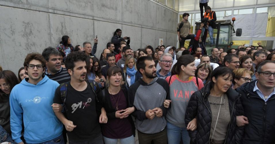 1.out.2017 -  Pessoas se reúnem para esperar a chegada da polícia na entrada de um local de votação em Barcelona, ??onde o presidente da Catanunha, Carles Puigdemont, deverá votar neste domingo