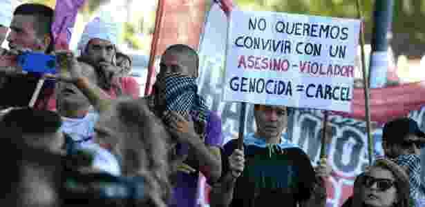 Ativistas protestam em frente à casa do ex-chefe da polícia de Buenos Aires, Miguel Etchecolatz, em Mar del Plata, depois que a Justiça permitiu que ele cumpra o resto de sua prisão perpétua em casa devido à sua idade avançada - Marina Devo/AFP