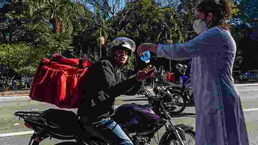 Entregador recebe álcool em gel distribuído na região da avenida Paulista, em São Paulo - Anderson Lira/ Framephoto/ Estadão Conteúdo