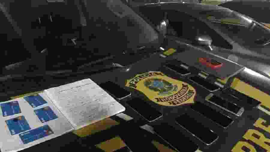 Em posse dos suspeitos, agentes da PRF encontraram dez celulares, um notebook e um caderno com números de CPF - Reprodução/PRF