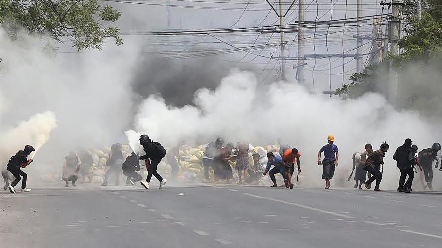 15.mar.2021 - Manifestantes fogem de gás lacrimogêneo disparado pelas forças de segurança em Mandalay, Mianmar - STR/AFP
