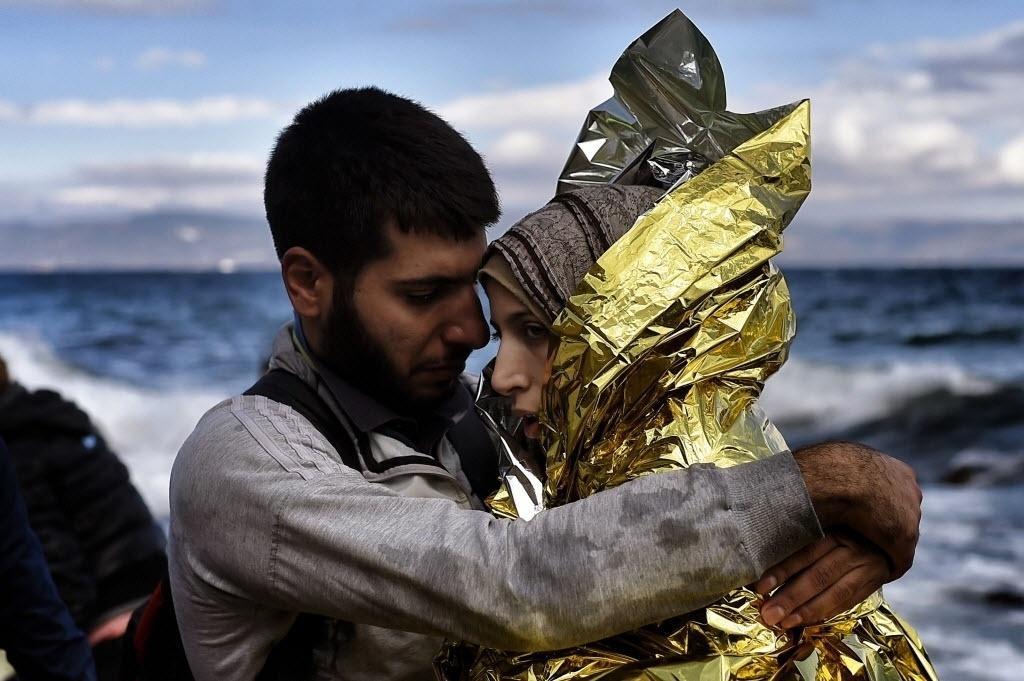 30.set.2015 - Refugiados se abraçam ao conseguir chegar na ilha grega de Lesbos, após atravessar o mar Egeu saindo da Turquia