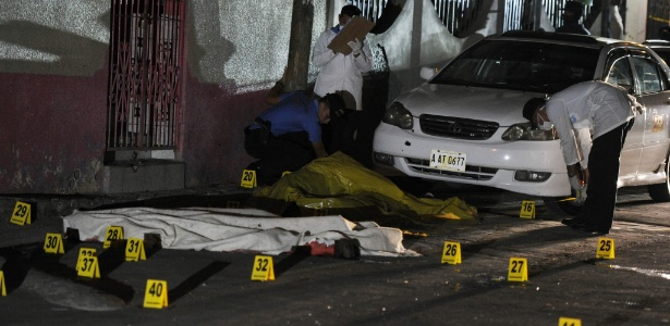 Especialistas forenses trabalham em local de massacre em guerra entre gangues em Tegucigalpa, capital de Honduras - Orlando Sierra/AFP