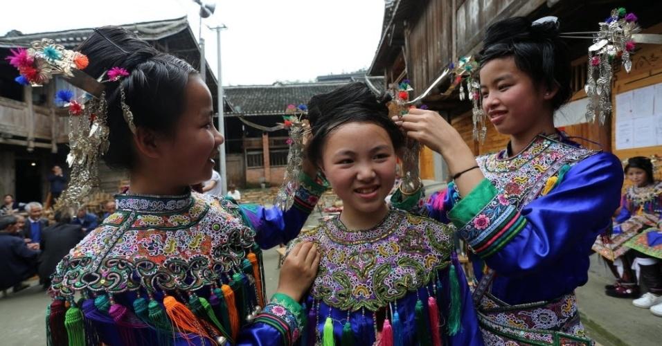 """3.mai.2016 - Grupo étnico de meninas se veste para celebrar o festival do """"Arroz no Bambu"""", na aldeia Dong Wugong, na China. Os moradores comem arroz preparado dentro de bambus para celebrar sua cultura"""