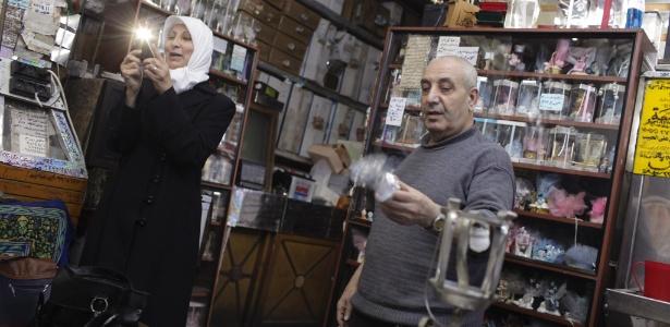 Adnan Gimaah, dono de uma loja de doces, com uma cliente, em Damasco, na Síria