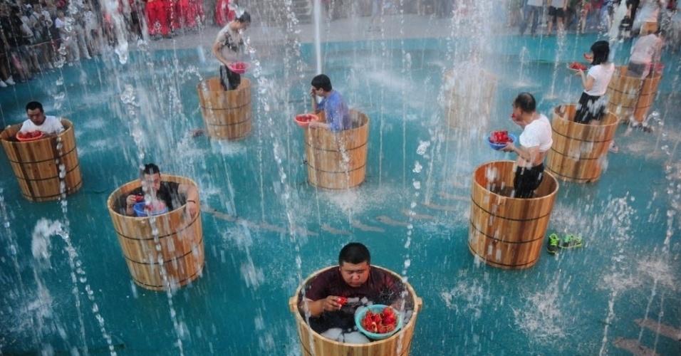 21.jul.2016 - Participantes comem pimenta enquanto tomam banho de água gelada em uma competição para ver quem come mais em menos tempo em Hangzhou, na China
