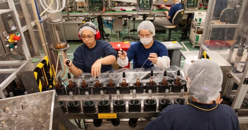 A fábrica é separada em três áreas de produção: o setor dos chamados não-alcóolicos (cremes e loções), o de hidroalcoólicos (colônias e desodorantes) e o de maquiagem. Na foto, funcionários colocam as válvulas em um dos perfumes produzidos