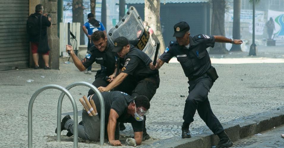 9.fev.2017 - Ao menos três policiais militares agridem homem que portava rojões durante confronto entre PMs e manifestantes nas imediações da Alerj, no Centro do Rio. Servidores do Estado protestam contra o pacote de austeridade do governo Pezão e a privatização da Cedae