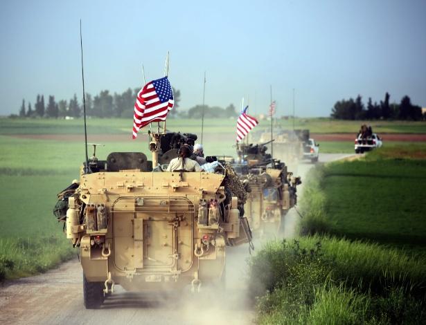 Forças armadas dos EUA, acompanhadas por combatentes das Unidades de Proteção do Povo Curdo (YPG), dirigem seus veículos blindados próximo a aldeia síria, na fronteira com a Turquia