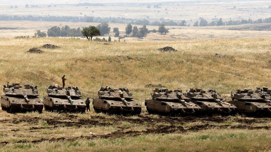 Tanques israelenses se posicionam nas colinas do Golã, área anexada por Israel na fronteira com a Síria. O exército israelense realizou ataques contra posições do Irã e do Hezbollah em resposta ao disparo de foguetes contra suas forças na região. As colinas do Golã foram ocupadas por Israel em 1967, durante a Guerra dos Seis Dias - Menahem Kahana/AFP
