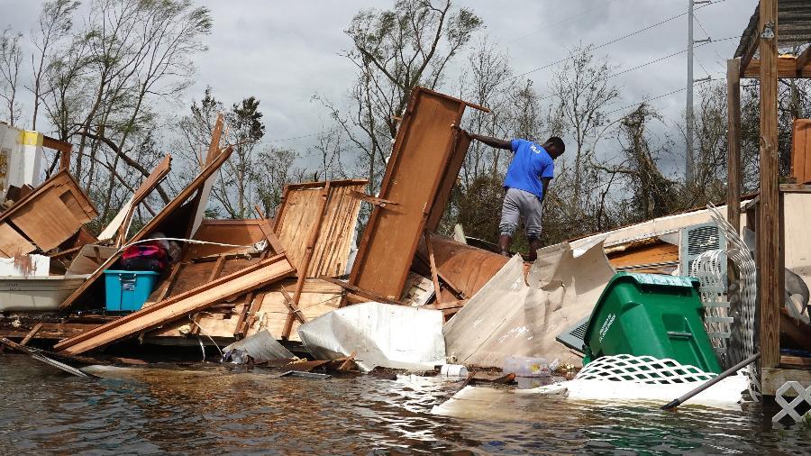 30.ago.21 - Homem resgata itens da casa de sua mãe após local ser destruído pelo furacão Ida em Laplace, Louisiana - SCOTT OLSON/Getty Images via AFP