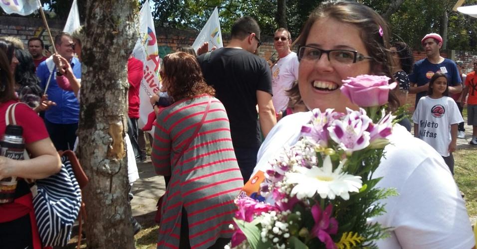 2.out.2016 - A estudante Carolina Barbosa entregou flores a ex-presidente Dilma Rousseff em frente à escola estadual Santos Dummont, na zona sul de Porto Alegre