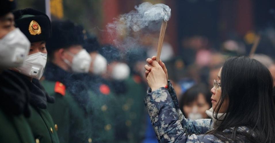 28.jan.2017 - Chinesa queima incenso durante oração por boa sorte no Templo Lama no primeiro dia do Ano Novo Chinês, em Pequim