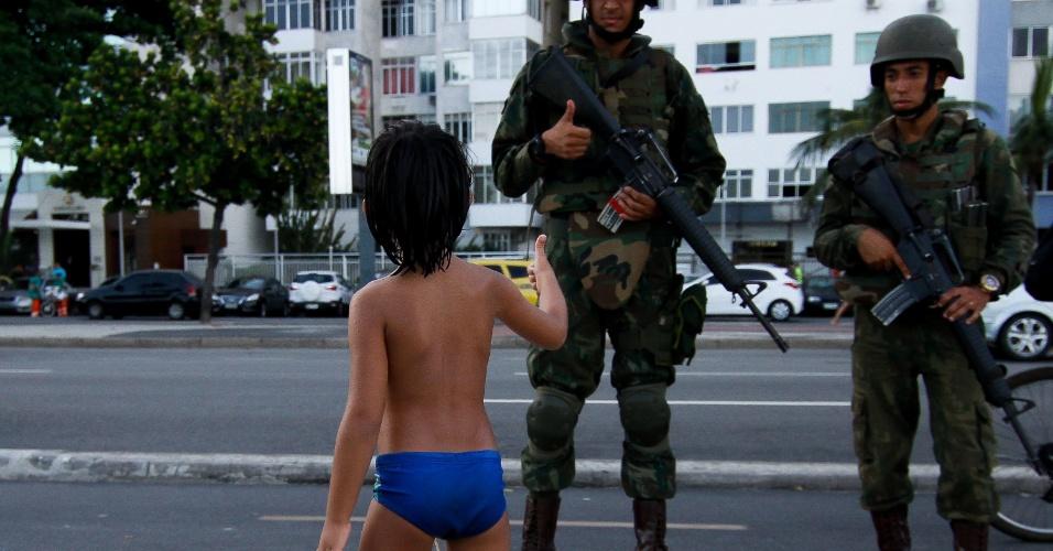 14.fev.2017 - Soldado do Exército cumprimenta criança durante patrulha na praia de Copacabana, no Rio