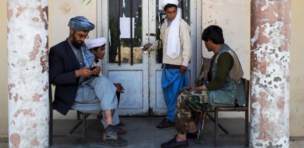 Um guarda e alguns estudantes em frente à entrada de um seminário, em Togh-Bairdi, no Afeganistão