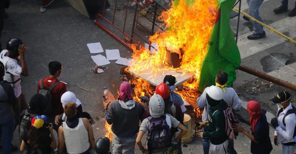30.jul.2017 - Manifestantes observam uma barricada sendo queimada após confrontos durante as eleições