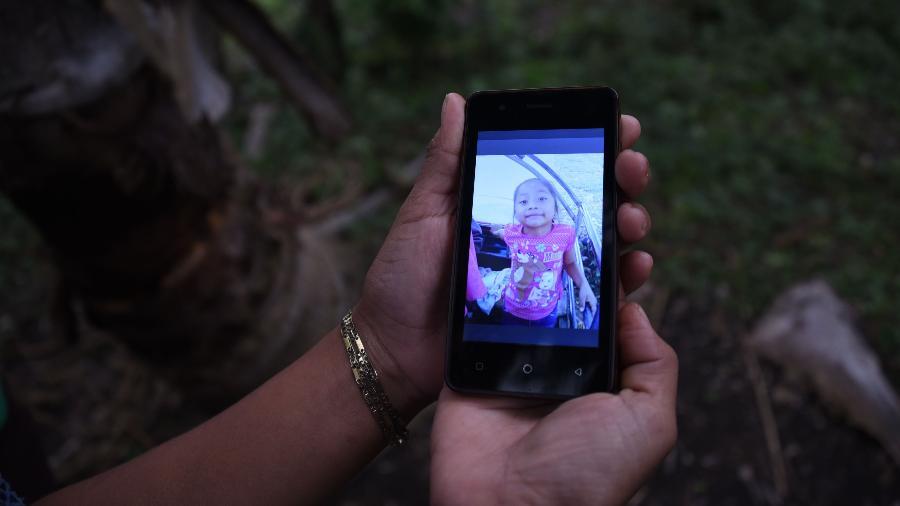 Familiar mostra, na tela de um celular, foto da garotinha Jakelin Amei Rosmery Caal, morta aos sete anos em um hospital do Texas dois dias depois de ter sido levada por agentes de fronteira norte-americanos no Novo México - Johan Ordonez/AFP