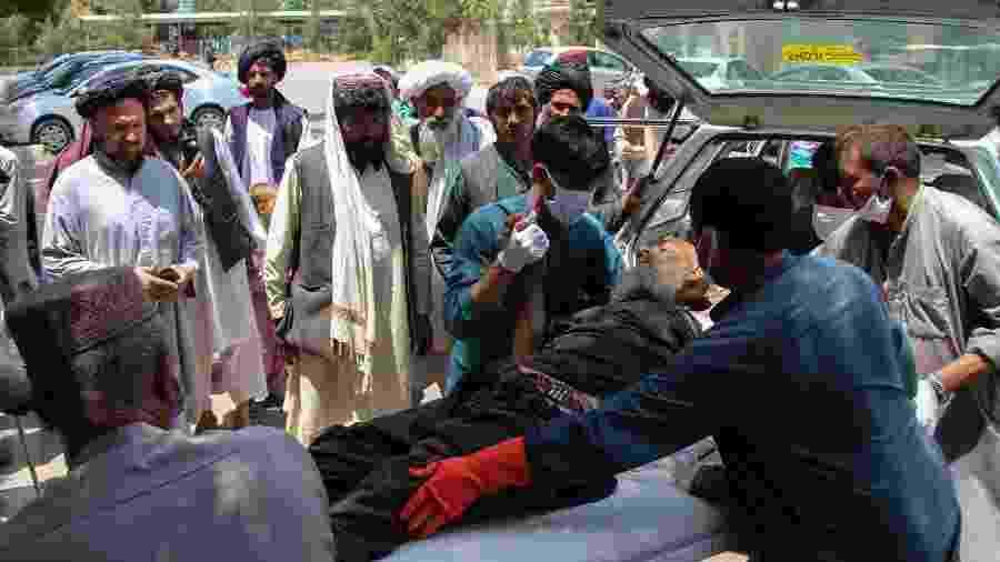 29.jun.2020 - Homem é carregado após se ferir em explosão em um mercado no sul do Afeganistão - Noor MOHAMMAD / AFP