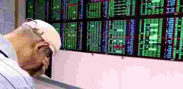 Investidor cobre o rosto em frente a painel da Bolsa de Taiwan, que caiu 4,84% hoje - David Chang/EFE