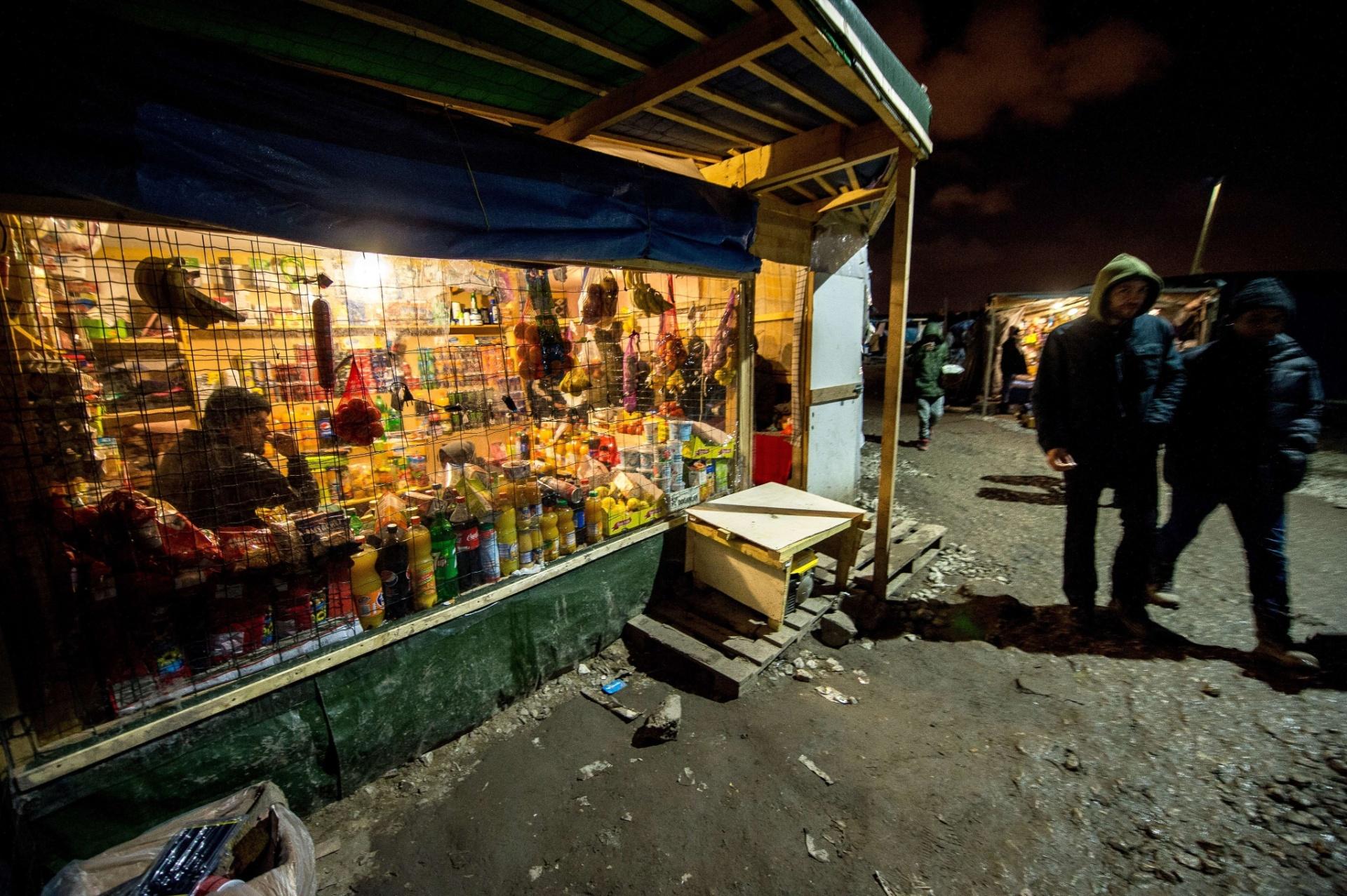 26.nov.2015 - Imigrantes passam por loja montada dentro do campo de refugiados improvisado em Calais (França) chamado de